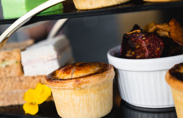 This ultimate afternoon tea is served with an array of savouries including these warm pork pies & crisps.