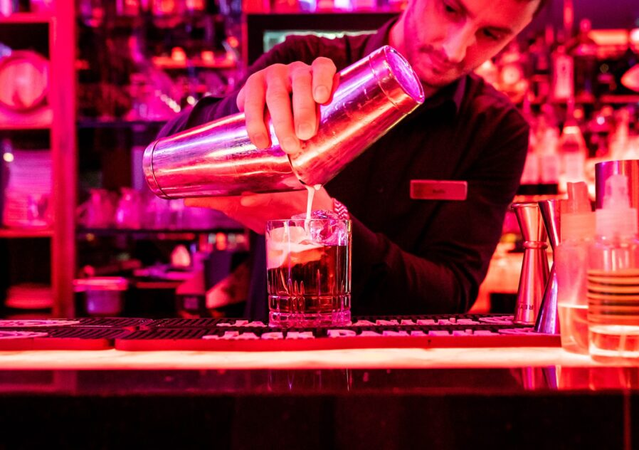 Bartender pouring a White Russian on the bar